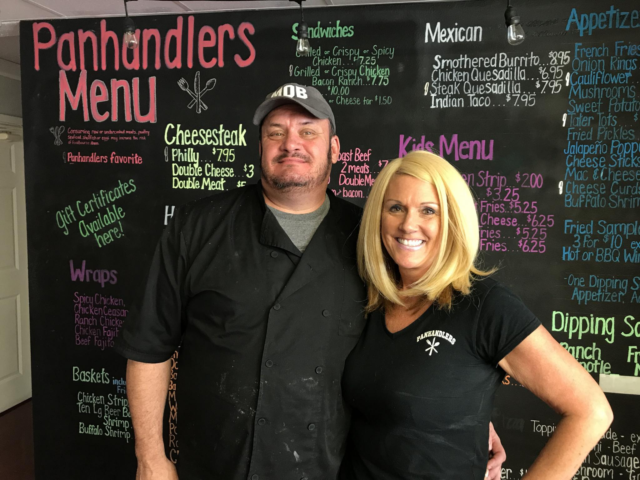 NLT | Becky Uehling<strong>John and Lori Thomason stand in front of their menu board at their restaurant Panhandlers in Oshkosh, Neb. </strong>